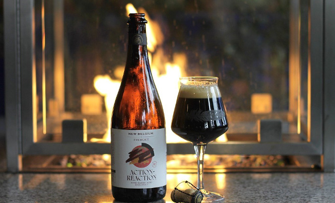 Bottle of action-reaction stout in front of a fireplace.